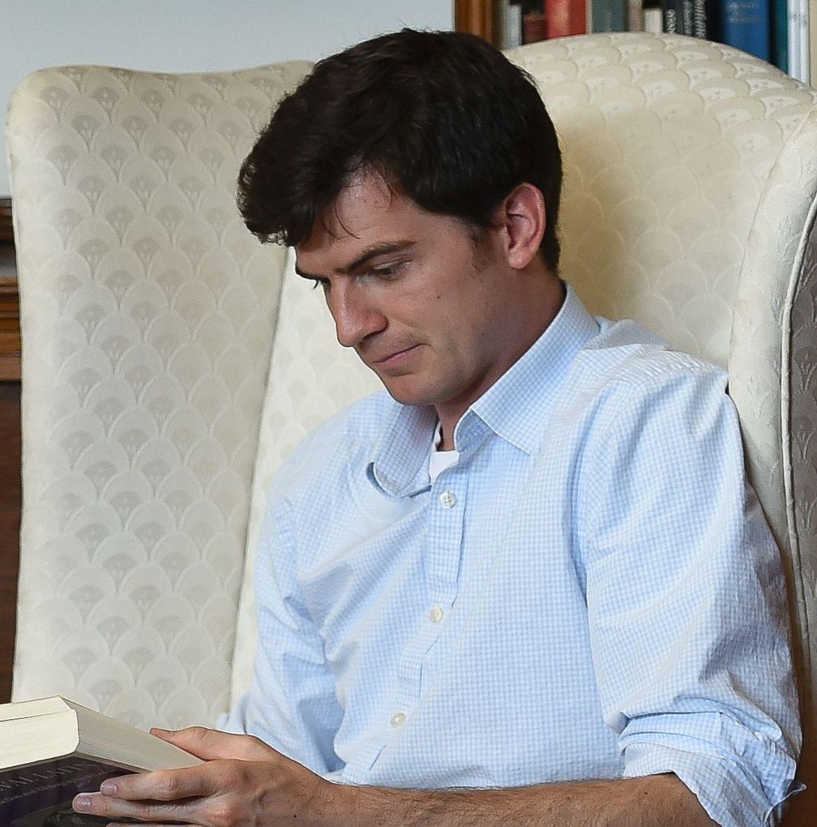 Doctoral Candidate Jon Paul Heyne reading a book
